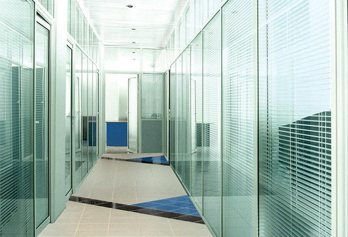 На фото прекрасный пример, как разделить большое помещение стеклянными перегородками со встроенными жалюзи