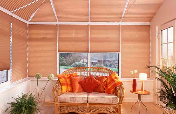 На фото хорошо видно, что легкие шторы плиссе позволяют красиво оформить самые сложные архитектурные формы