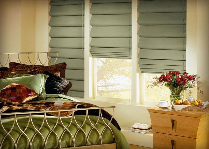 На фото идея дизайна спальной комнаты римскими занавесями